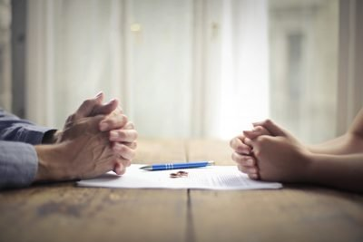 couples' hands with divorce settlement agreement between them