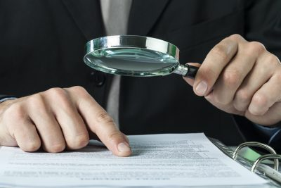 estate planning fraud | close up of hands holding magnifying glass